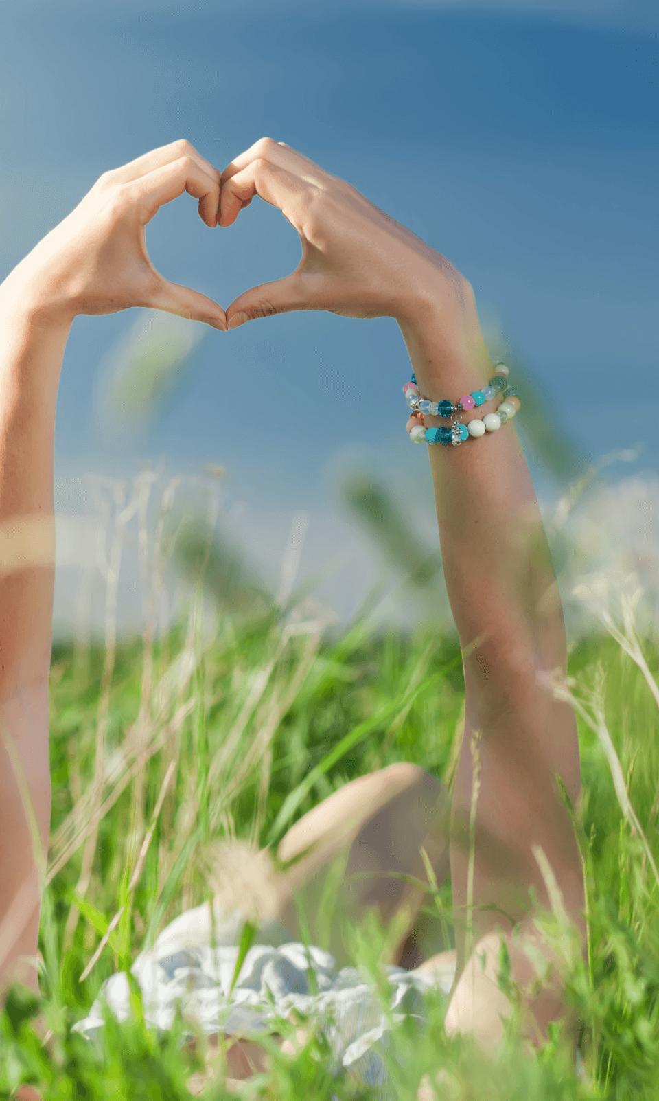 Un engagement humain fort. L'image représente une personne allongée dans l'herbe formant un coeur avec ses mains