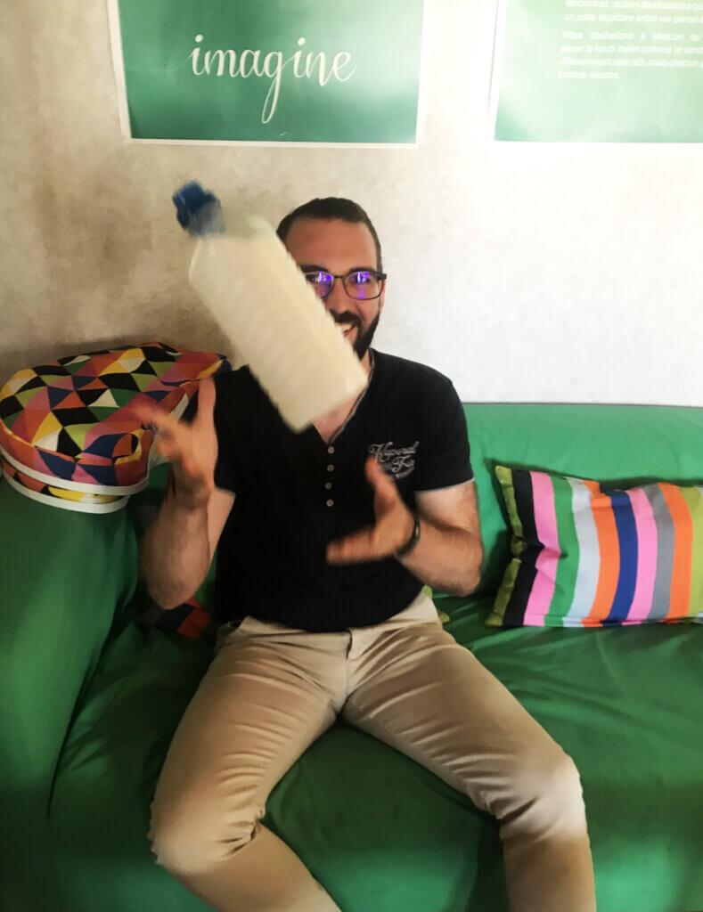 Mickael Durand lançant en l'air son bidon de lessive fait maison, sur un canapé vert, chez Locam